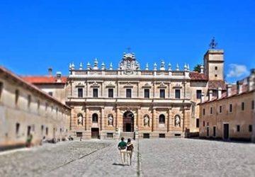 Facciata della Certosa di san Lorenzo e casa bassa con due turisti che camminano